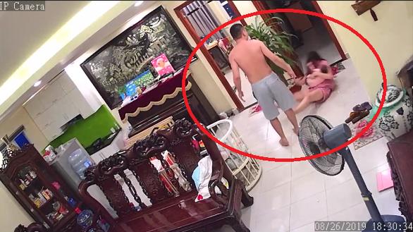 Người chồng đánh vợ đang bế con ngã ra sàn nhà (Ảnh cắt từ clip)