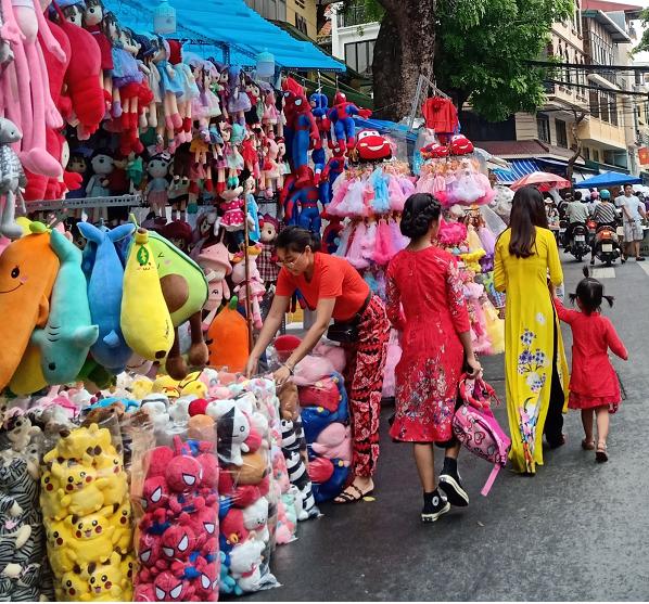 1. Nhiều người tranh thủ vừa tham quan, mua sắm trên phố Hàng Mã và chụp ảnh lưu niệm giữa không gian rực rỡ sắc màu