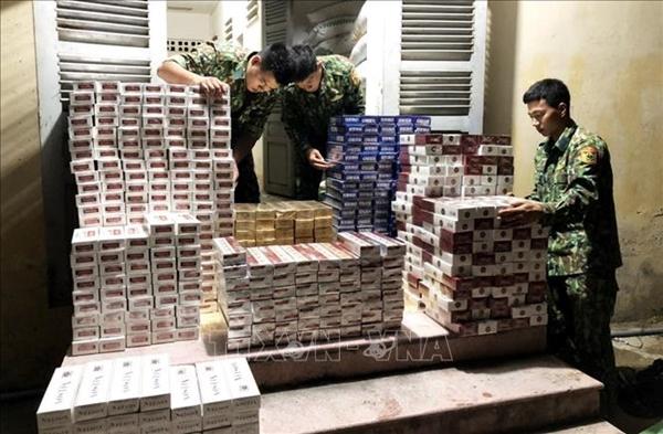 Cán bộ, chiến sĩ Đồn Biên phòng quốc tế Tịnh Biên kiểm đếm số tang vật vừa thu giữ trong một vụ buôn lậu thuốc lá điếu từ Campuchia vào Việt Nam (Ảnh: Công Mạo/TTXVN)