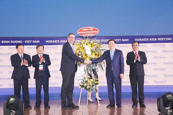 Phó thủ tướng Chỉnh phủ Vương Đình Huệ tặng lẵng hoa chúc mừng Diễn đàn kinh tế châu Á Horasis 2019 thành công tốt đẹp. Ảnh: M.Khánh