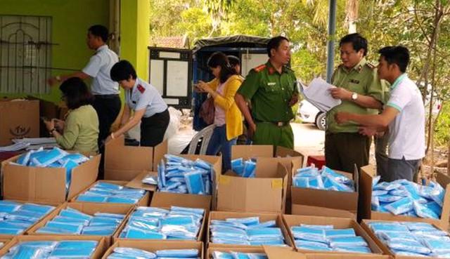 Lực lượng chức năng kiểm tra, tạm giữ các thùng khẩu trang y tế tại Công ty TNHH Dược Tâm Hưng.
