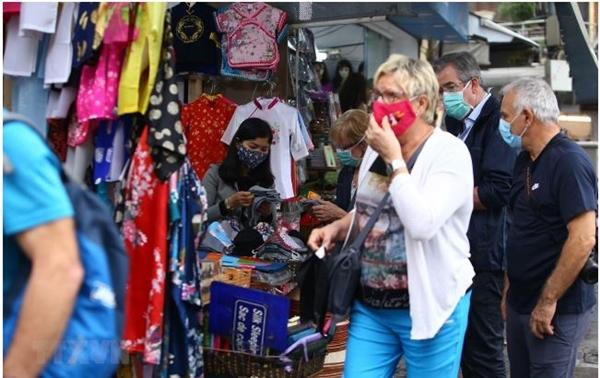 Khách du lịch nước ngoài đeo khẩu trang khi tham quan, mua sắm ở Việt Nam trong thời kỳ dịch Covid-19 (Ảnh: Minh Quyết/TTXVN)