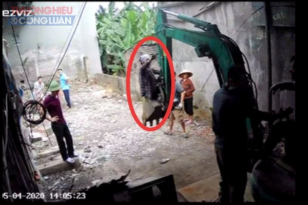 Bà Định, vợ ông Nho trèo lên gầu máy xúc để cản trở việc thi công