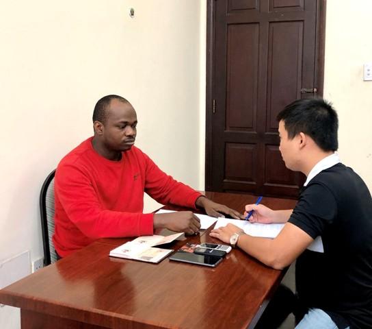 Điều tra viên lấy lời khai Chukwugekwe Godwin Ajearo  (áo đỏ)