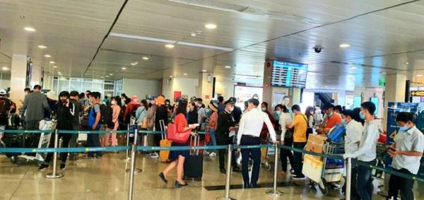 Hành khách xếp hàng chờ làm thủ tục check-in của Vietnam Airlines tại Tân Sơn Nhất (Ảnh: CÔNG TRUNG)