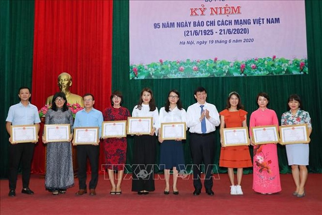 Thứ trưởng Bộ Y tế Nguyễn Thanh Long trao Bằng khen tặng các cá nhân đã có thành tích xuất sắc trong công tác thông tin, tuyên truyền về phòng chống dịch COVID-19. Ảnh: Thành Đạt/TTXVN