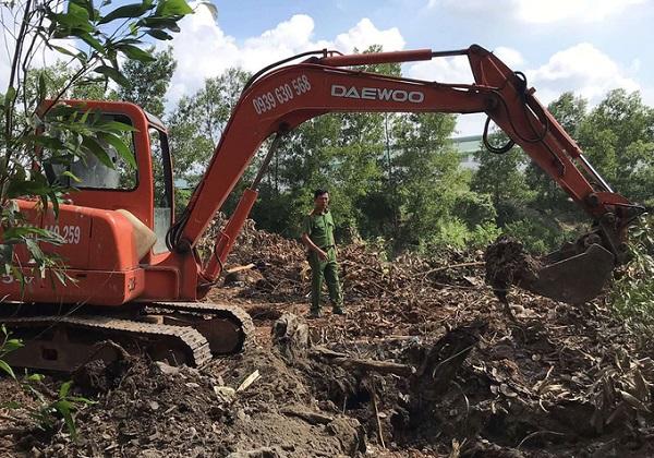 Công an khai quật hố chôn rác thải trong khuôn viên công ty (Ảnh: Thái Hà)