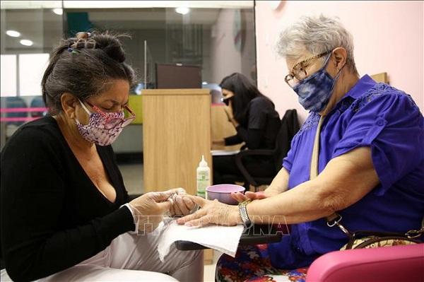 Người dân đeo khẩu trang phòng lây nhiễm COVID-19 tại một cửa hàng làm tóc ở Sao Paulo, Brazil, ngày 6/7 (Ảnh: THX/TTXVN)