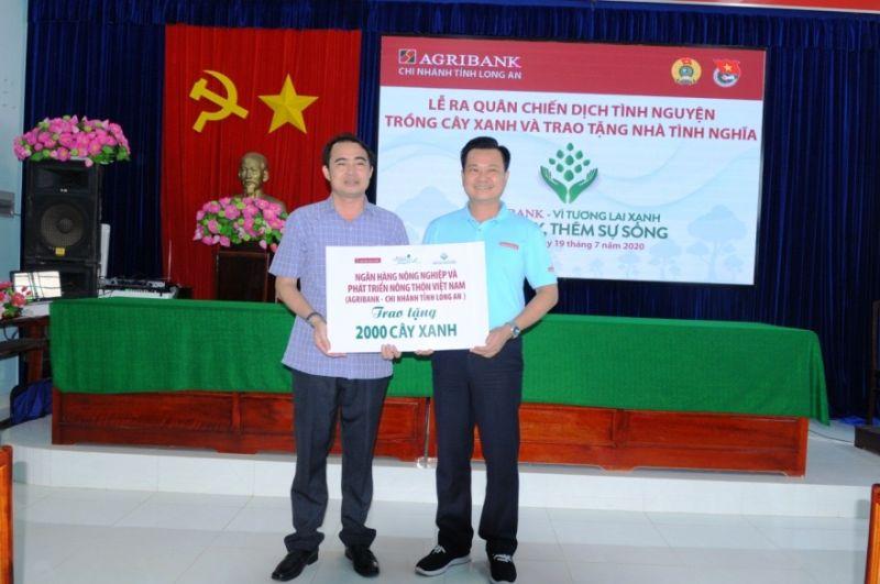 Ông Nguyễn Trí Dũng - Phó Giám đốc Agribank Chi nhánh tỉnh Long An trao bảng tượng trưng tặng 2.000 cây xanh cho địa phương