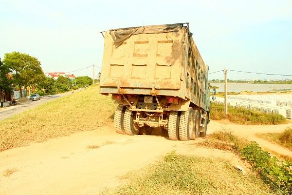 Xe trọng tải lớn chở vật liệu chạy cắt mặt đê mùa mưa bão