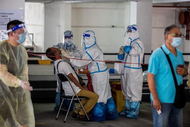 Nhân viên y tế lấy mẫu dịch xét nghiệm COVID-19 cho người dân tại Hong Kong, Trung Quốc ngày 19/7/2020. Ảnh: AFP/TTXVN