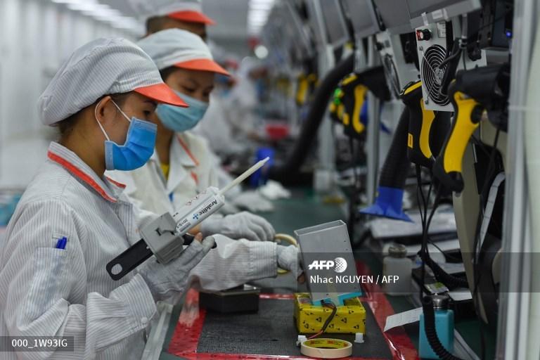 """Nữ công nhân đang vận hành dây chuyền sản xuất máy thở tại nhà máy Vsmart - những thiết bị hiện đại quan trọng sẽ được sử dụng để điều trị bệnh nhân nhiễm virus COVID-19. Hiện tại, sản phẩm máy thở mang thương hiệu Vsmart đã được sản xuất hàng loạt, sẵn sàng hỗ trợ ngành y tế đối phó với đại dịch. Hình ảnh được đăng tải trong bài """"WHO tuyên bố sẽ khó có vắc-xin điều trị triệt để COVID-19"""" của hãng thông tấn AFP."""