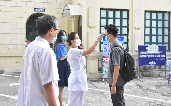 Thí sinh được đo thân nhiệt trước khi vào phòng thi tại Hà Nội.