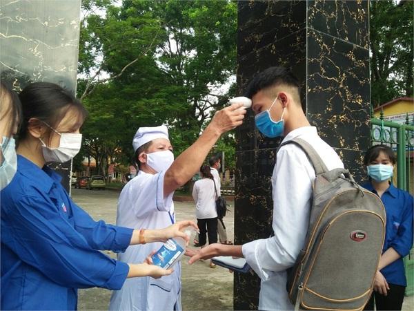 Cán bộ y tế đo thân nhiệt cho thí sinh tại điểm thi THPT Tam Đảo (Tam Đảo)