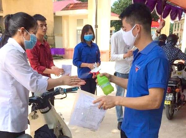 Các tình nguyện viên đang  xịt nước rửa tay sát khuẩn cho các thí sinh trước khi bước vào phòng thi.