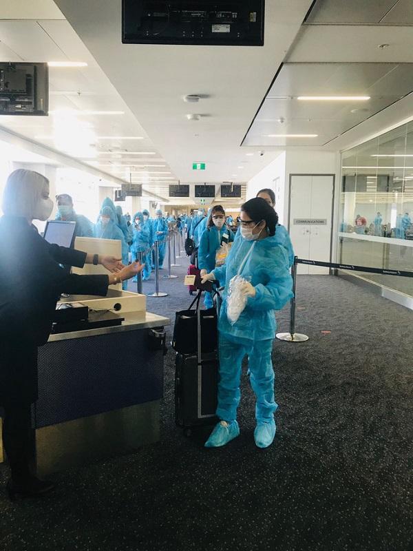 Công dân được trang bị đồ bảo hộ toàn thân trước khi lên máy bay về nước