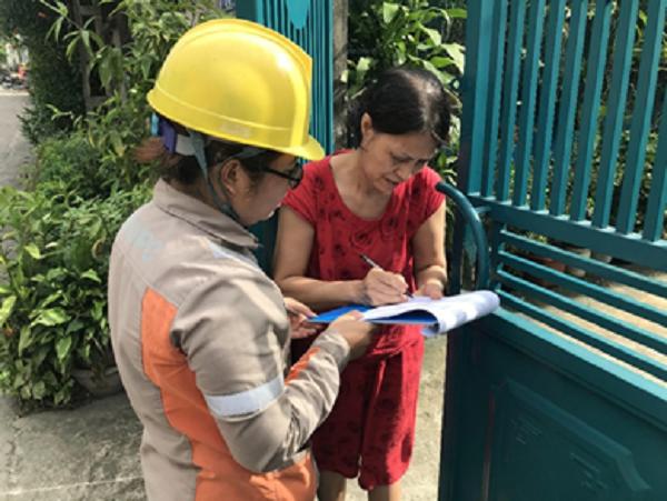 Công nhân điện lực hướng dẫn bà Trịnh Thị Nguyệt - tổ dân phố 12 phường Đồng Quang (TP. Thái Nguyên) ký biên bản thay thế công tơ cơ khí bằng công tơ điện tử