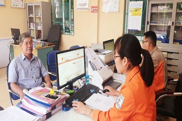 Giao dịch viên đang hướng dẫn khách hàng đăng ký tài khoản và mua điện qua Cổng Dịch vụ công Quốc gia