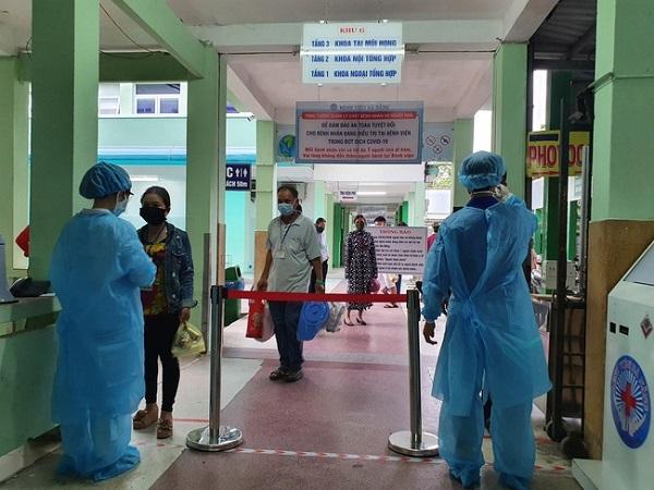 Nhân viên y tế kiểm tra thân nhiệt cho người dân đến viện
