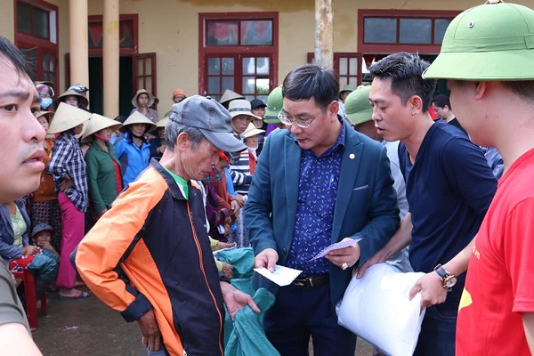Ông Nguyễn Ngọc Quyết (ở giữa) - TBT Tạp chí Điện tử Hòa nhập trao quà cứu trợ cho bà con nhân dân vùng lũ thôn Phú Hòa, xã Phú Thuỷ, huyện Lệ Thuỷ, Quảng Bình.