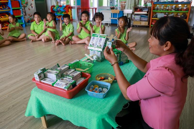 Giáo viên trường Mầm non Thị trấn Củ Chi 2 (TP HCM) hướng dẫn các em làm đồ chơi từ vỏ hộp sữa đã uống.