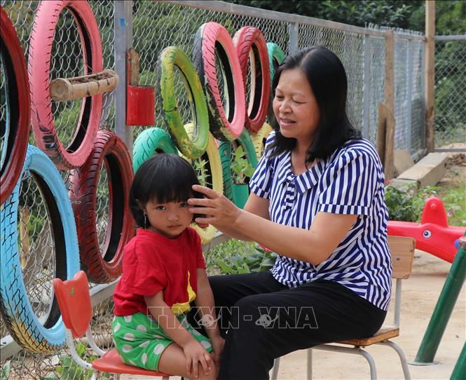 Cô giáo Lê Thị Loan chăm sóc, chải tóc cho học sinh của mình.Ảnh: Xuân Tiến/TTXVN