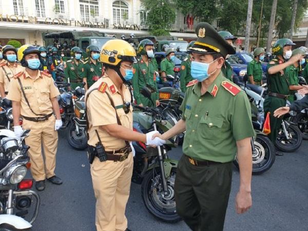 Thiếu tướng Lê Hồng Nam - Giám đốc Công an TPHCM bắt tay khích lệ tinh thần của các chiến sĩ trước giờ ra quân. Ảnh: CHÍ THẠCH