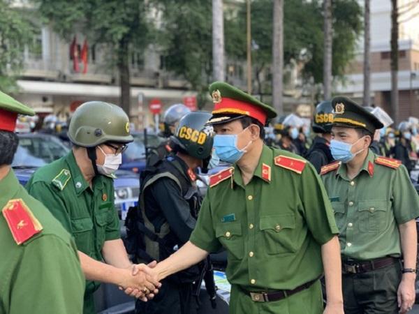 Lãnh đạo Công an TPHCM bắt tay khích lệ tinh thần của các chiến sĩ trước giờ ra quân. Ảnh: CHÍ THẠCH