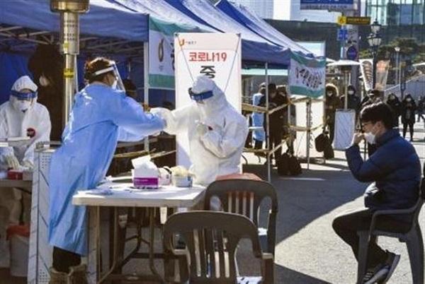 Nhân viên y tế lấy mẫu xét nghiệm Covid-19 cho người dân tại Seoul, Hàn Quốc ngày 14/12/2020 (Ảnh: Kyodo/TTXVN)
