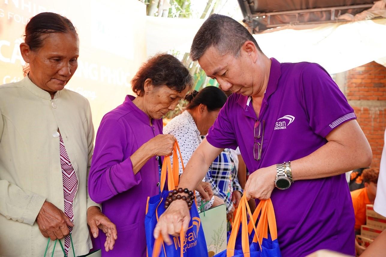 Nhân viên công ty Cổ phần Hàng tiêu dùng Masan trao quà cho các em học sinh và bà con