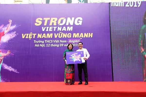 Đại diện Ban lãnh đạo CLB Bóng đá Hà Nội tặng quà cho nhà trường để sắm giáo cụ thể chất cho các em học sinh