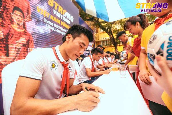 Các cầu thủ ký tặng các em học sinh