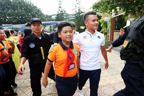 Quang Hải vui vẻ bước vào cùng các em học sinh
