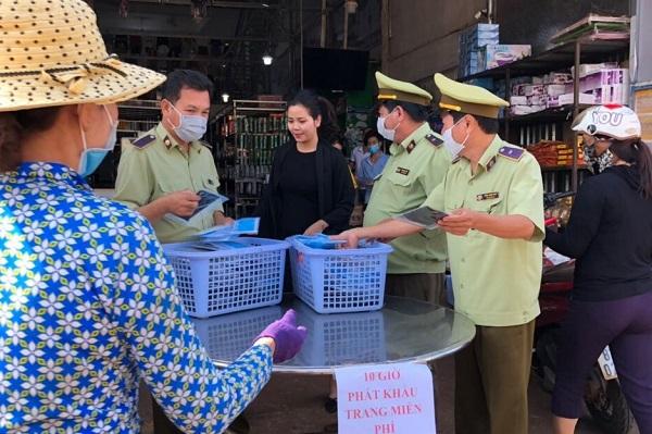 Phối hợp cùng các cá nhân, tổ chức cấp phát khẩu trang cho người dân (Ảnh: Cục QLTT Gia Lai)