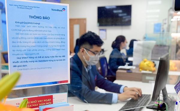 Cán bộ, nhân viên VietinBank hướng dẫn khách hàng sát khuẩn, đeo khẩu trang trước khi vào giao dịch.
