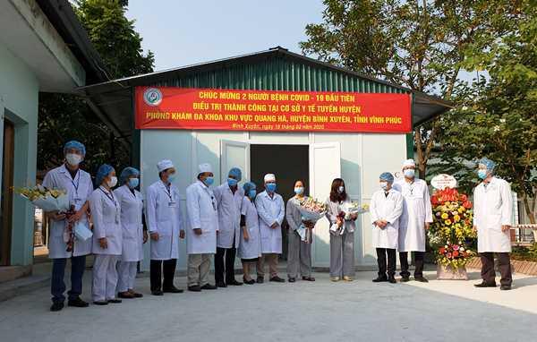 Đại diện Sở Y tế Vĩnh Phúc tặng hoa chúc mừng hai bệnh nhân đã được điều trị khỏi Covid-19 tại Bình Xuyên