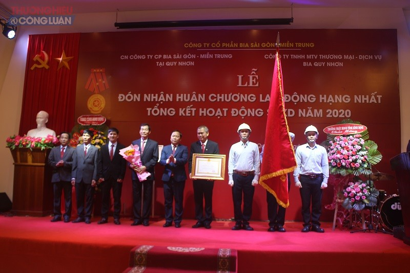 Phó Bí thư Tỉnh uỷ, Chủ tịch UBND tỉnh Nguyễn Phi Long (ở giữa -bên trái) trao Huân chương Lao động hạng Nhất của Chủ tịch nước cho tập thể Chi nhánh CTCP bia Sài Gòn -Miền Trung tại Quy Nhơn