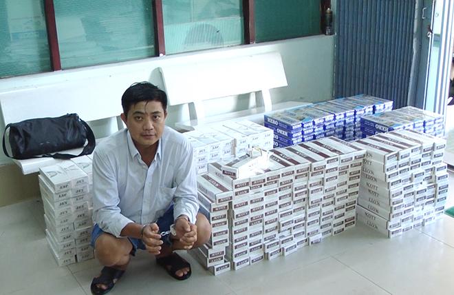 Đối tượng Trần Dũng Tiến và số thuốc lá lậu bị bắt giữ