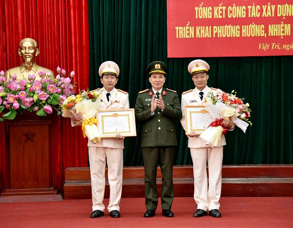 Giám đốc Công an tỉnh Phạm Trường Giang trao Huy hiệu 30 năm tuổi Đảng cho 2 cá nhân.