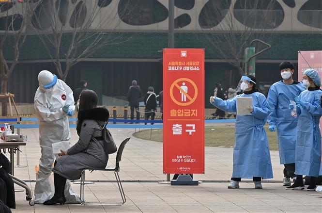 Nhân viên y tế lấy mẫu dịch xét nghiệm Covid-19 cho người dân tại Seoul, Hàn Quốc, ngày 23/12/2020 (Ảnh: AFP/ TTXVN)