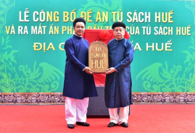 Chủ tịch UBND tỉnh Phan Ngọc Thọ (bên phải) trao logo Tủ sách Huế cho cơ quan quản lý