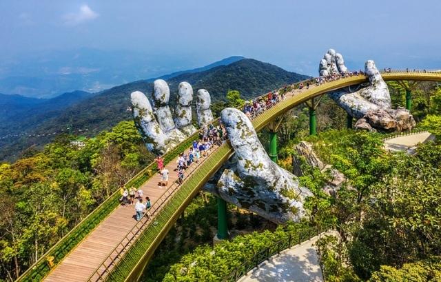 """Cầu Vàng (cầu bàn tay) với kiến trúc độc đáo được khánh thành năm 2018 tại Đà Nẵng. Cây cầu dài 150m, có độ cao 1.441m so với mực nước biển và mang điểm nhấn là hai đôi bàn tay đây rêu phong """"đỡ"""" cây cầu. Cầu Vàng đã trở thành địa điểm chụp ảnh yêu thích của du khách khi đến Đà Nẵng."""