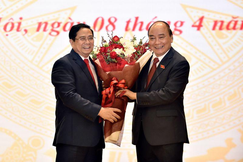 Thủ tướng Phạm Minh Chính tặng hoa Chủ tịch nước Nguyễn Xuân Phúc tại lễ bàn giao công việc. Ảnh: VGP/Quang Hiếu