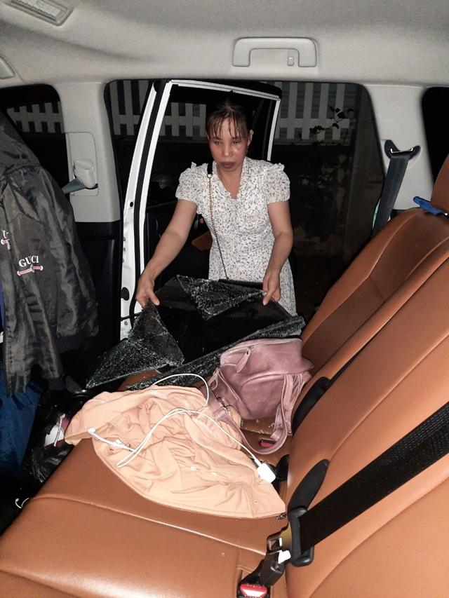 Chị Liên (vợ anh Toàn) dọn những mảnh kính vỡ rơi vào trong xe