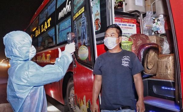 Nhân viên y tế trong trang phục phòng dịch đang đo thân nhiệt cho tài xế tại chốt kiểm tra