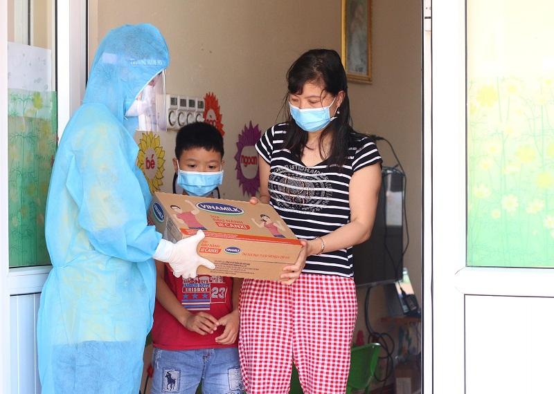 Người dân, trẻ em trong nơi cách ly tập trung tại huyện Thuận Thành, một trong những điểm nóng về dịch ở Bắc Ninh, đón nhận món quà từ Vinamilk
