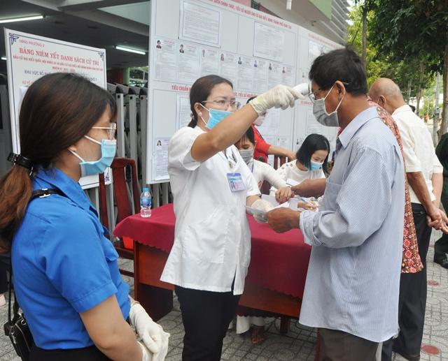 Các cử tri được đo thân nhiệt, khai báo y tế và xịt nước sát khuẩn ngay từ khâu đầu tiên