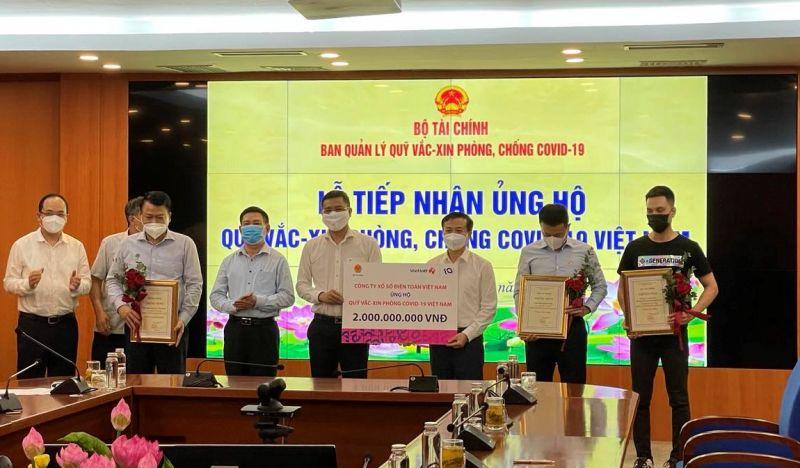Đại diện Vietlott trao tặng 2 tỉ đồng đến Quỹ Vắc–xin phòng COVID-19 Việt Nam. Ảnh: KT