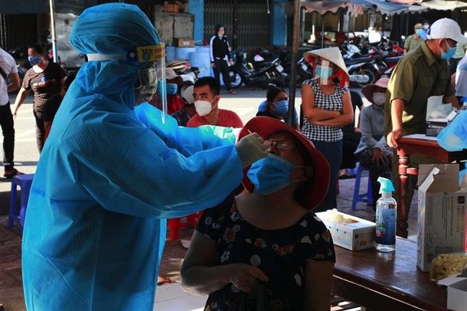 Nhân viên y tế lấy mẫu xét nghiệm người dân ở khu vực chợ La Gi, ngày 13/7