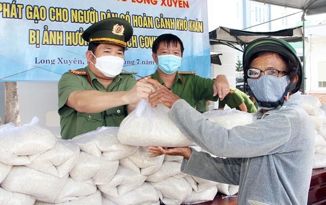 Đại tá Đinh Văn Nơi, Giám đốc Công an tỉnh An Giang động viên, trao tặng gạo cho người dân khó khăn. Ảnh: Trần Lĩnh